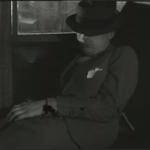 un homme dort dans le même compartiment de train, le chapeau rabattu sur les yeux