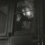 le train entre en gare ; le jeune garçon regarde par la vitre du train pour voir son ami monter