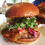 photographie d'un hamburger composé de plusieurs tranches de bœuf haché, de tranches de tomates, de feuilles de salade et d'oignon. Le tout déborde.